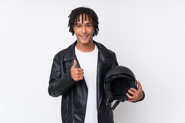 Giovane uomo afroamericano che tiene un casco del motociclo isolato sulla parete bianca con i pollici su perché è successo qualcosa di buono