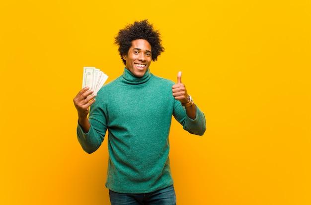 Giovane uomo afroamericano con le banconote in dollari contro la parte posteriore dell'arancia