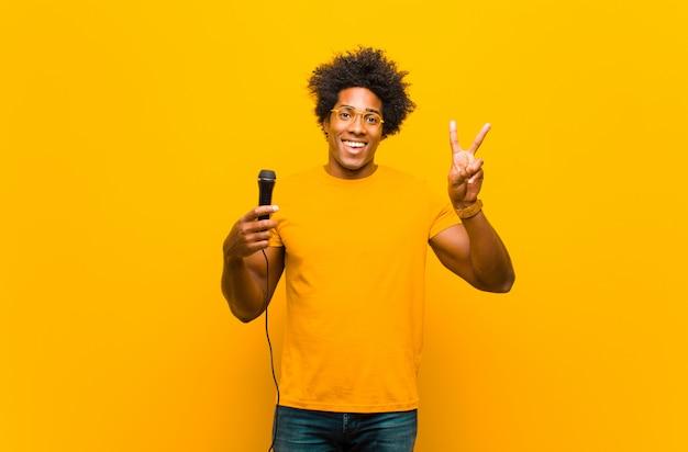 Giovane uomo afroamericano con un canto del microfono