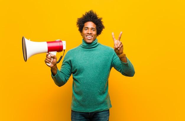 Giovane uomo afroamericano con un megafono contro backg arancio