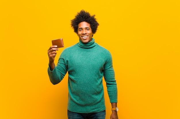 Giovane uomo afroamericano con un portafoglio contro il backgrou arancio