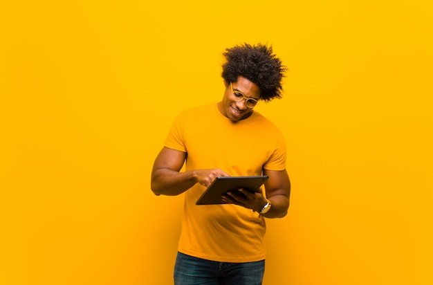 Giovane uomo afroamericano con una compressa contro l'arancia