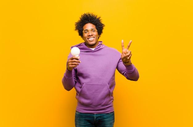 Giovane uomo afroamericano con una lampadina contro la parte posteriore dell'arancia