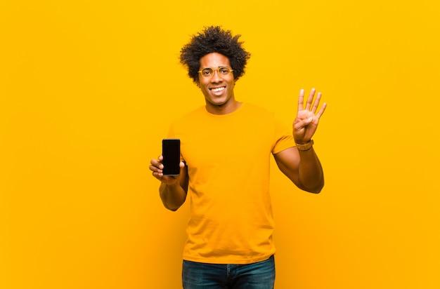 Giovane uomo afroamericano con uno smart phone contro il bac arancio