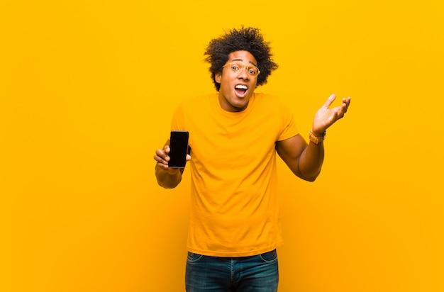 Giovane uomo afroamericano con uno smart phone contro l'arancia