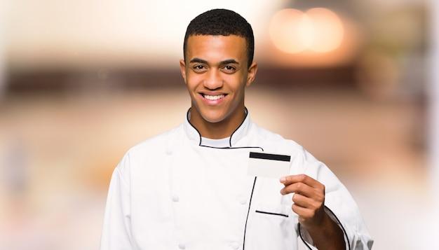 Giovane uomo afroamericano del cuoco unico che tiene una carta di credito sulla parete unfocused
