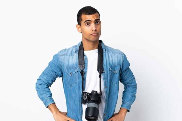 Giovane uomo afroamericano del fotografo sopra la parete bianca isolata triste