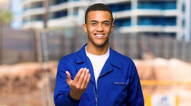 Giovane uomo afroamericano del lavoratore che invita a venire con la mano.