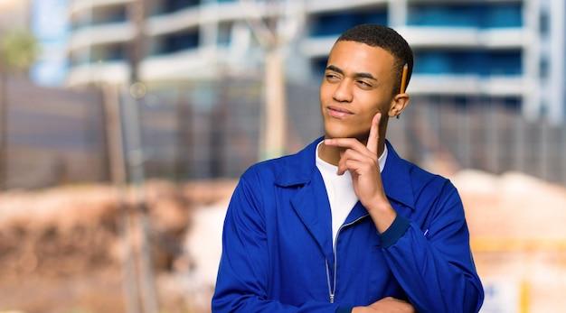 Giovane uomo afroamericano del lavoratore che pensa un'idea mentre cercando in un cantiere