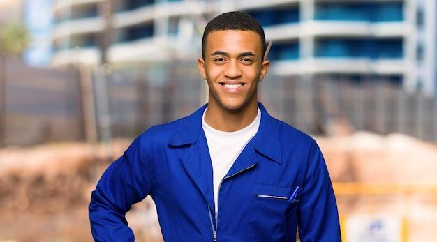 Giovane uomo afroamericano del lavoratore che posa con le armi all'anca e che sorride in un cantiere