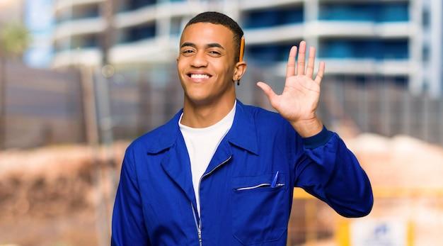 Giovane uomo afroamericano del lavoratore che saluta con la mano con l'espressione felice in un cantiere