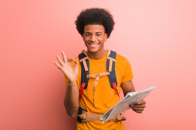 Giovane uomo afroamericano dell'esploratore che tiene una mappa allegra e sicura facendo gesto giusto