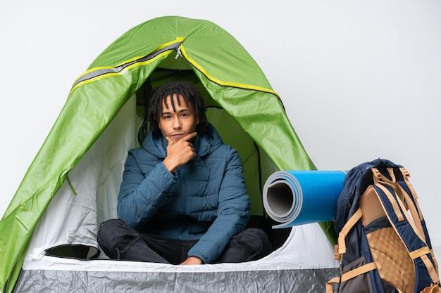 Giovane uomo afroamericano dentro un pensiero verde di campeggio della tenda