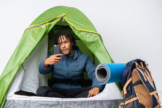 Giovane uomo afroamericano dentro una tenda verde di campeggio che fa un selfie