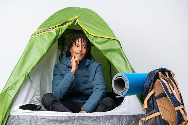 Giovane uomo afroamericano dentro una tenda verde di campeggio che pensa un'idea mentre cercando