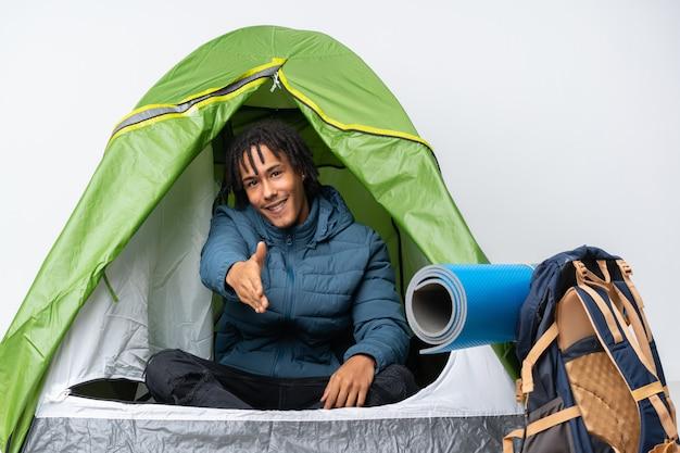 Giovane uomo afroamericano dentro una tenda verde di campeggio che stringe le mani per chiudere molto