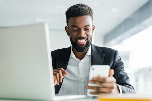 Giovane uomo afroamericano di affari che utilizza telefono e che fa gesto del vincitore con il pugno nell'ufficio