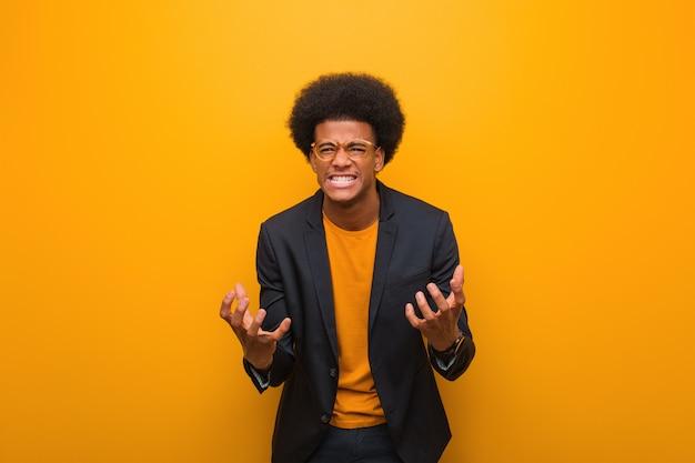 Giovane uomo afroamericano di affari sopra una parete arancio arrabbiata e turbata