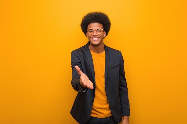 Giovane uomo afroamericano di affari sopra una parete arancione che raggiunge fuori per accogliere qualcuno