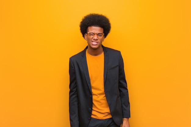 Giovane uomo afroamericano di affari sopra una parete arancione che sbatte le palpebre, gesto divertente, amichevole e spensierato