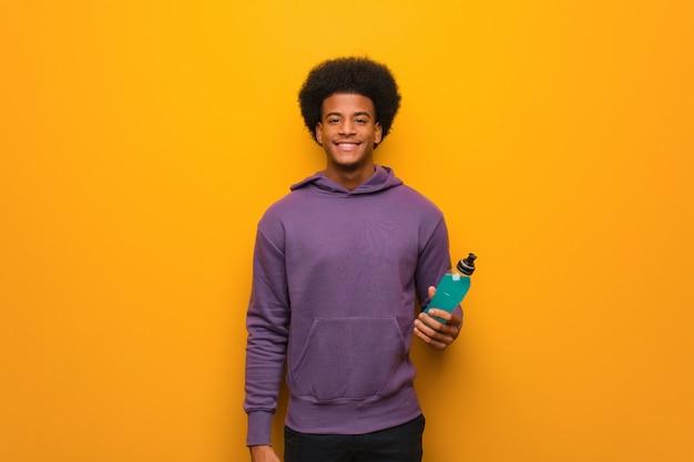 Giovane uomo afroamericano di forma fisica che giudica una bevanda energetica allegra con un grande sorriso