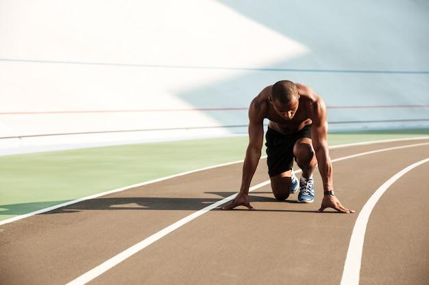 Giovane uomo afroamericano di sport nella posizione di partenza pronto per iniziare sulla pista di sport allo stadio
