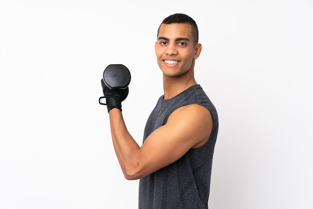 Giovane uomo afroamericano di sport sopra la parete bianca isolata che fa sollevamento pesi