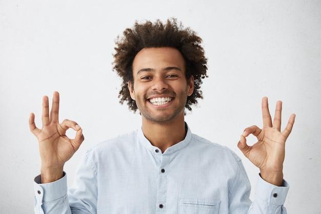 Giovane uomo afroamericano felice spensierato con l'acconciatura funky che mostra segno giusto