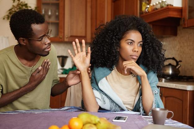 Giovane uomo afroamericano infelice dispiaciuto con gli occhiali che si sforza di parlare dolcemente la sua moglie offensiva pazza che è seduta accanto a lui al tavolo della cucina, rifiutando tutte le sue bugie. persone e relazioni