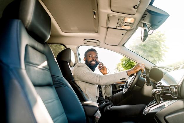 Giovane uomo afroamericano nell'abbigliamento casual astuto di affari, facendo uso del telefono che si siede nell'automobile, vista laterale