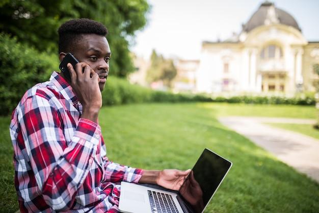 Giovane uomo afroamericano parla al telefono mentre era seduto sull'erba verde con il computer portatile sulla strada della città