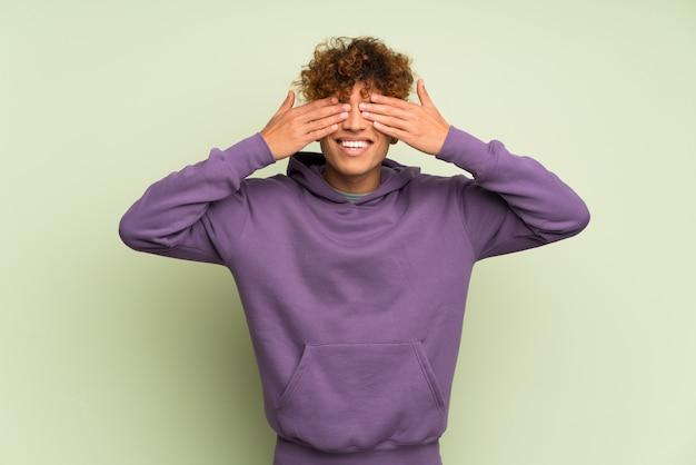 Giovane uomo afroamericano sopra gli occhi verdi isolati della copertura di parete a mano