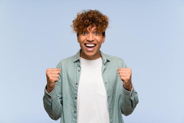 Giovane uomo afroamericano sopra isolato muro blu celebra una vittoria nella posizione del vincitore