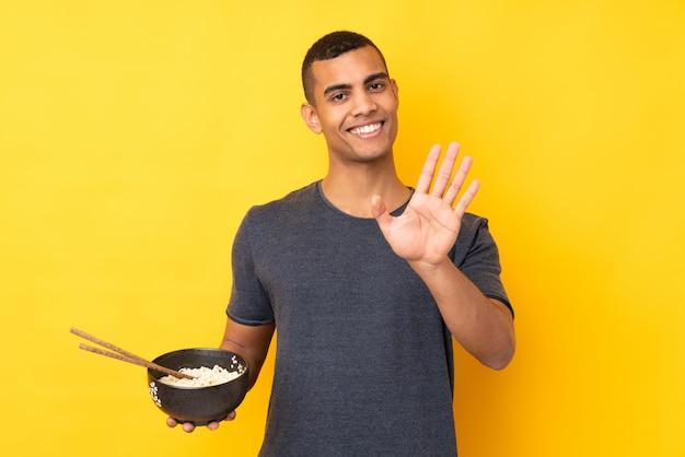 Giovane uomo afroamericano sopra la parete gialla isolata che saluta con la mano con l'espressione felice mentre tiene una ciotola di tagliatelle con le bacchette