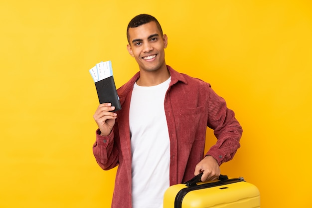 Giovane uomo afroamericano sopra la parete gialla isolata in vacanza con la valigia e il passaporto