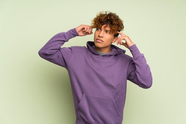 Giovane uomo afroamericano sopra la parete verde isolata avendo dubbi e pensando