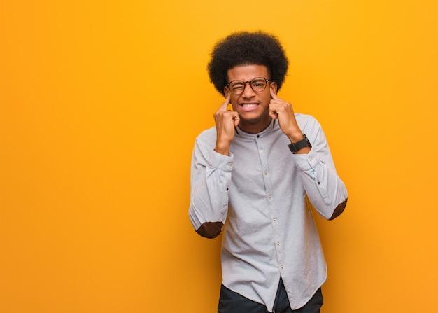 Giovane uomo afroamericano sopra le orecchie arancio del rivestimento murale con le mani