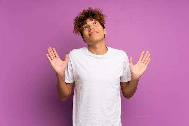 Giovane uomo afroamericano sopra muro viola isolato facendo dubbi gesto