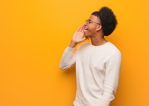 Giovane uomo afroamericano sopra un sottotono di pettegolezzo sussurrando muro arancione