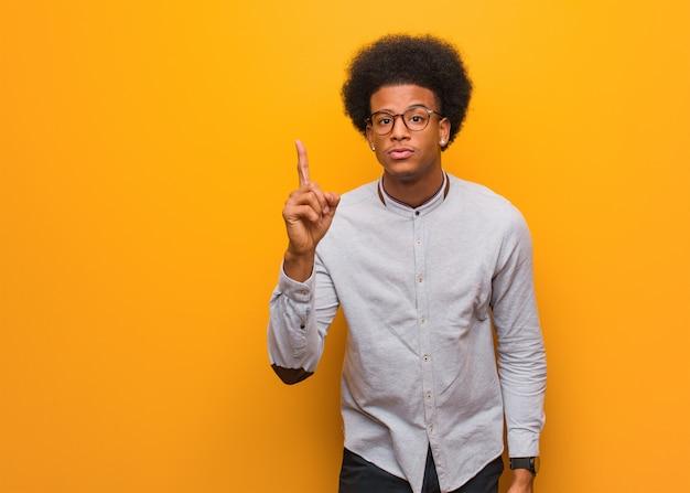 Giovane uomo afroamericano sopra una parete arancio che ha un'idea, concetto di ispirazione