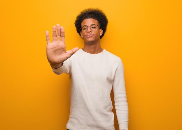 Giovane uomo afroamericano sopra una parete arancio che mette la mano nella parte anteriore