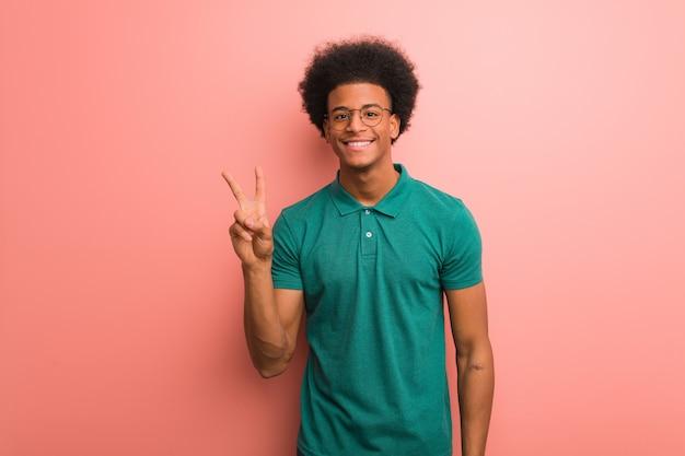 Giovane uomo afroamericano sopra una parete rosa divertente e felice facendo una vittoria gesto