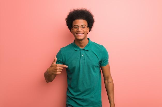 Giovane uomo afroamericano sopra una persona rosa della parete che indica a mano uno spazio della copia della camicia, fiero e sicuro