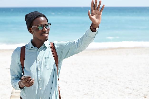 Giovane uomo afroamericano sorridente positivo amichevole in cappello alla moda e tonalità che tengono smartphone e agitando la mano, chiamando amici mentre si cammina sulla spiaggia della città