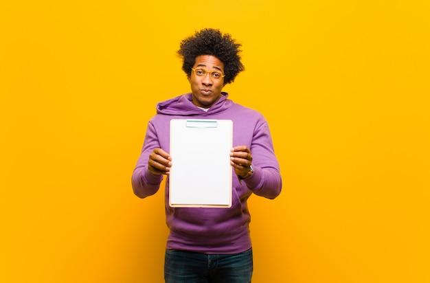 Giovane uomo afroamericano su sfondo arancione