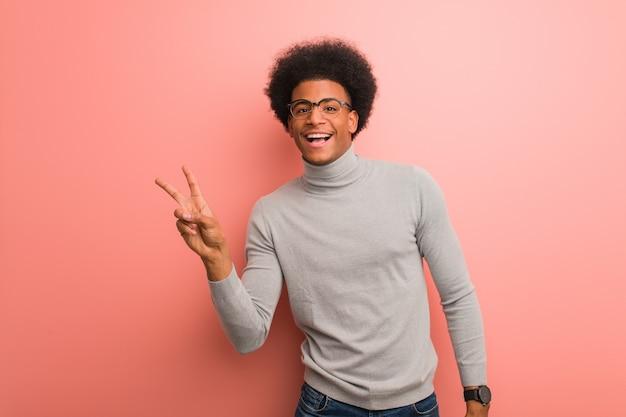 Giovane uomo afroamericano su un muro rosa facendo un gesto di vittoria