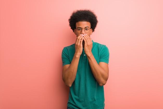 Giovane uomo afroamericano su una parete rosa molto spaventato e spaventato nascosto