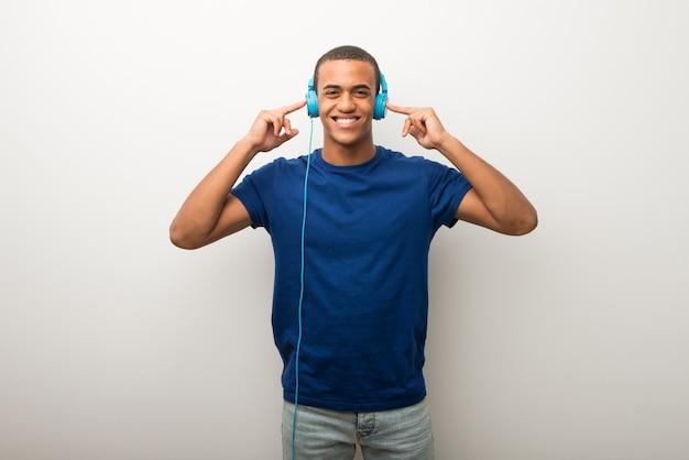Giovane uomo afroamericano sulla parete bianca che ascolta la musica con le cuffie