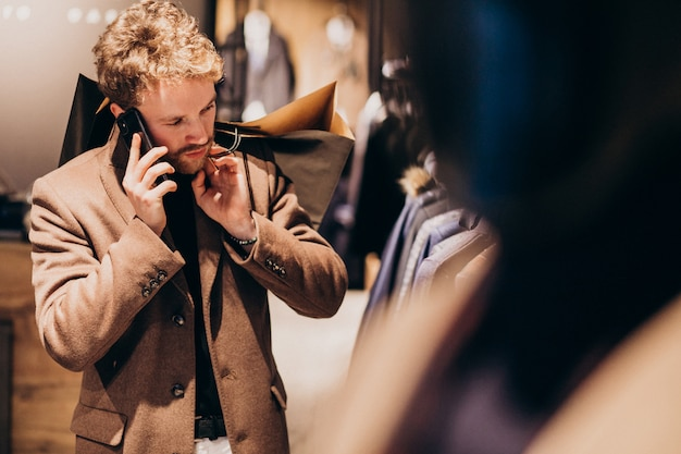 Giovane uomo al negozio di abbigliamento maschile parlando al telefono