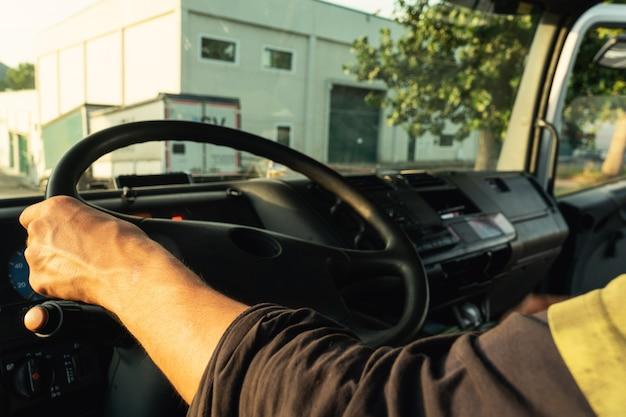 Giovane uomo alla guida di un camion all'interno della cabina con i vestiti di sicurezza